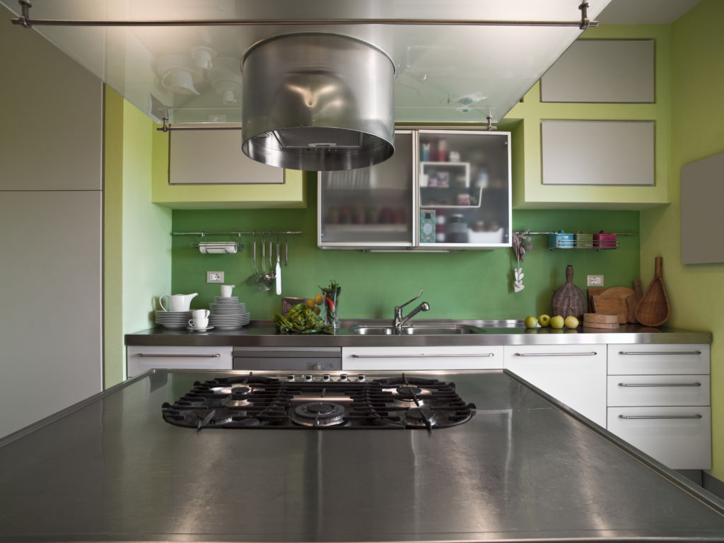 interior shot of a modern kitchen in foreground the gas hob and the extractor hood in background the kitchen cabinets abd the sink